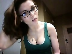 Geeky brunette displays her delicious cleavage in a green t